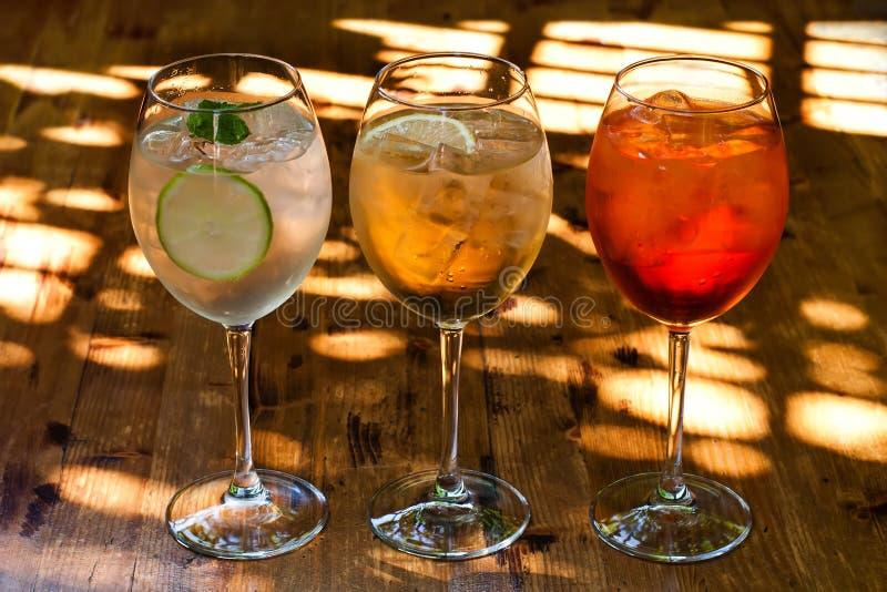 De cocktails van de mousserende wijnchampagne: aperol spritz, sprizz spriss, martini royale houten lijstachtergrond, zonneschijn royalty-vrije stock foto's