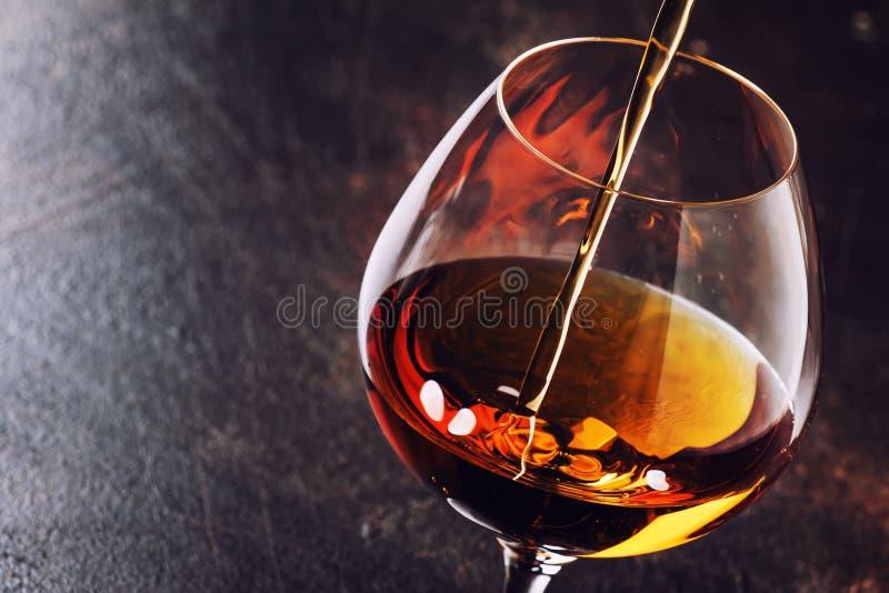 De cognac giet in Glas, Uitstekende Bruine Achtergrond, Selectieve Focu royalty-vrije stock foto