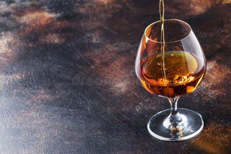 De cognac giet in Glas, Uitstekende Bruine Achtergrond, Selectieve Focu stock afbeeldingen