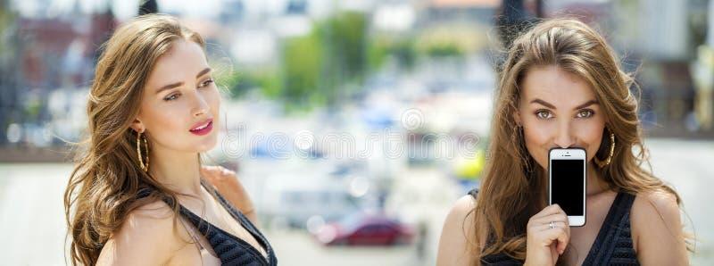 De collage, twee vrouwen behandelt haar slimme telefoon van het gezichtsscherm royalty-vrije stock afbeeldingen