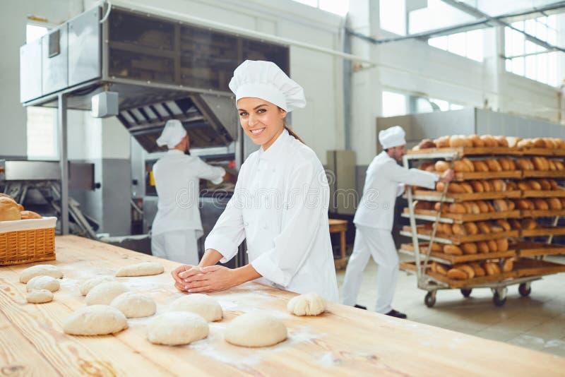 De collega's van een vrouwenbakker smileswith bij een bakkerij stock foto
