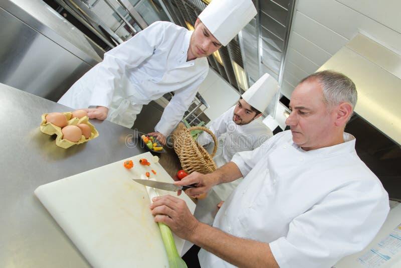 De collega's van het hoofd-chef-kokonderwijs hoe te om groenten te snijden stock afbeelding