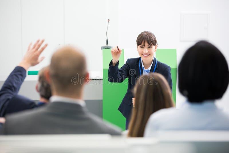 De Collega's van onderneemsterasking questions to terwijl het Geven van Presentatie stock foto