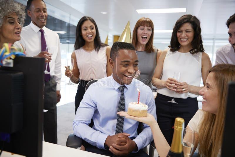 De collega's verzamelden zich bij een bureau van manï ¿ ½ s om een verjaardag te vieren stock foto