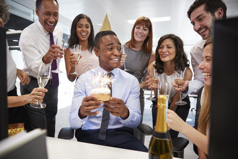De collega's verzamelden zich bij een bureau van manï ¿ ½ s om een verjaardag te vieren royalty-vrije stock fotografie