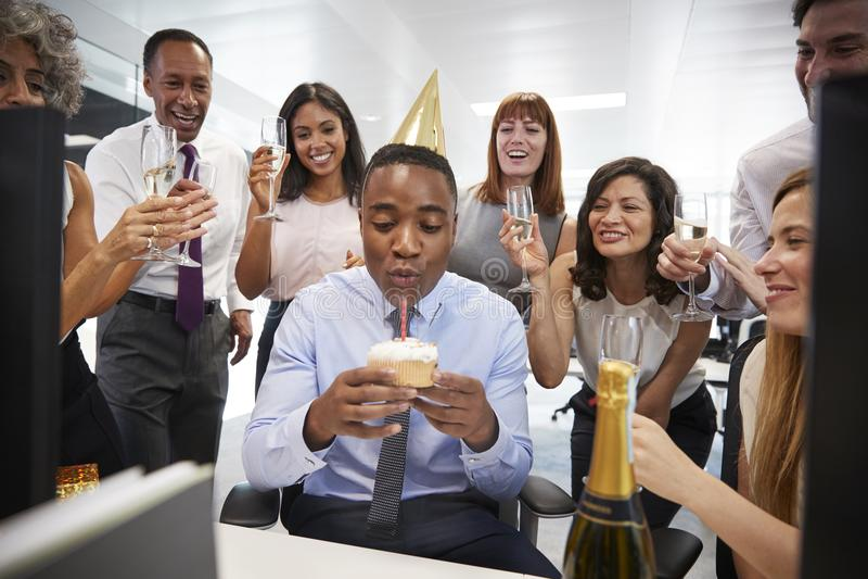 De collega's verzamelden zich bij een bureau van manï ¿ ½ s om een verjaardag te vieren royalty-vrije stock afbeelding