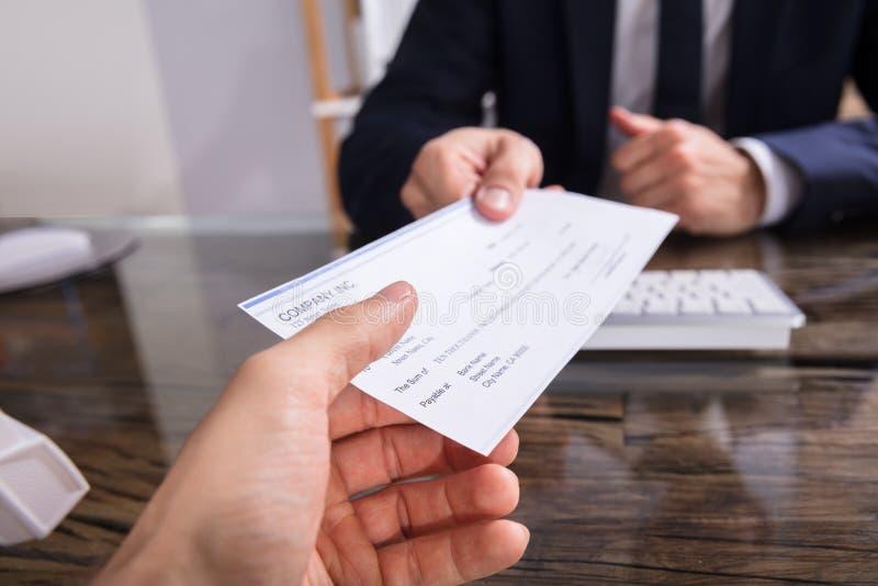 De Collega van Businesspersongiving cheque to stock afbeeldingen