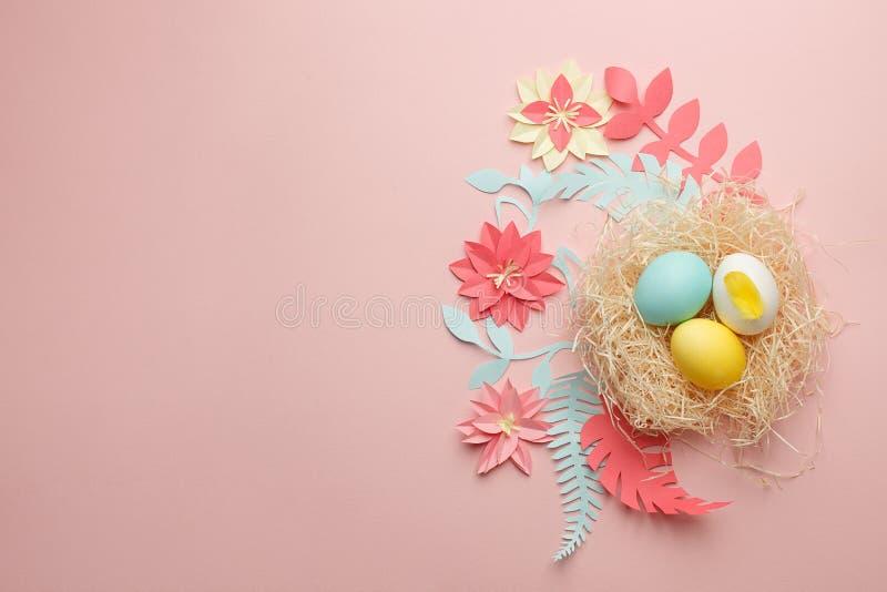 De Coloefulpaaseieren in nest op pastelkleurachtergrond met origami papercraft bloeien decoratie Exemplaarruimte, groetkaart stock fotografie