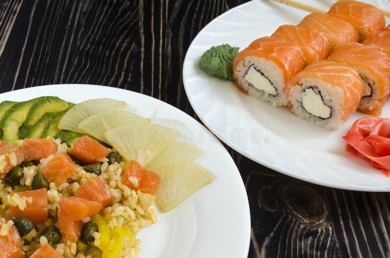 De color salmón con arroz y verduras en una placa blanca del sushi con los salmones en una opinión oscura del primer del fondo de fotos de archivo
