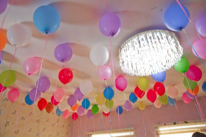 De Colorfullballons drijven op het witte plafond in de ruimte voor de partij Huwelijk of van de kinderenverjaardag het binnenland stock afbeelding