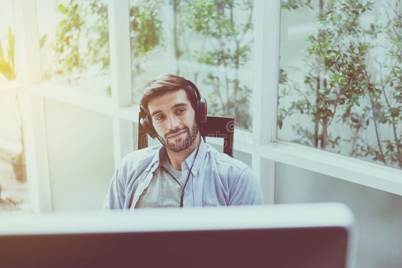 De comfortabel knappe mens met baard gebruikend hoofdtelefoon en thuis luisterend aan muziek, Gelukkig en glimlachend, ontspant t royalty-vrije stock afbeeldingen