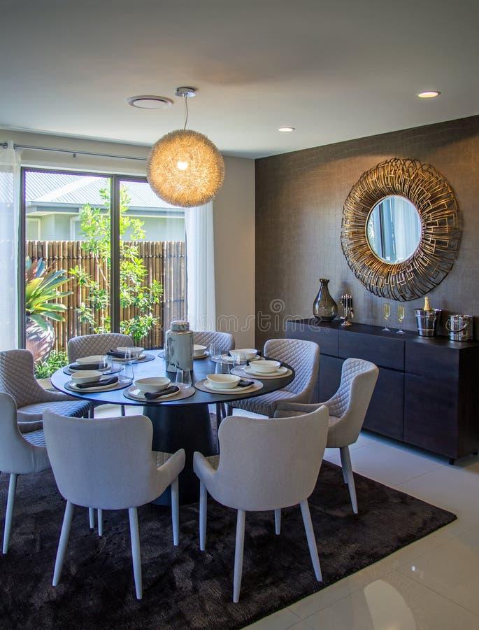 De comfortabele eetkamer met acht stoelspiegel op muur kijkt uit aan bamboeomheining stock foto's