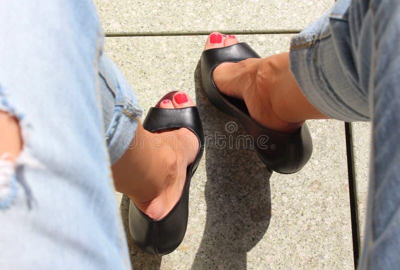 De comfortabele en manieruitrusting aan hoge stad, jeans en zwarte hielt schoenen stock fotografie