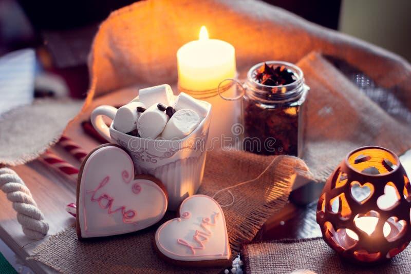 De comfortabele winter met kaarsen en de kop van koffie met heemst en gember breken in de vorm van hart Stilleven voor St Valenti stock afbeeldingen