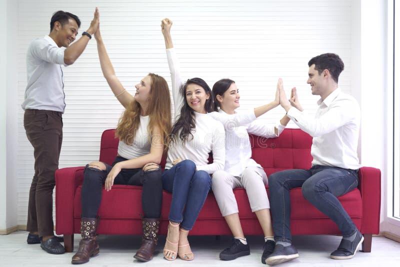 De communautaire vrienden die van de diversiteitsgroep die mensen gelukkige pret en lachen hebben samen, op rode bank, de samenho royalty-vrije stock foto