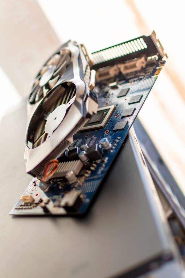 De componenten van een persoonlijk bureaubladcomputer een gedemonteerde raads videokaart met een koeler ligt op het geval van een stock foto