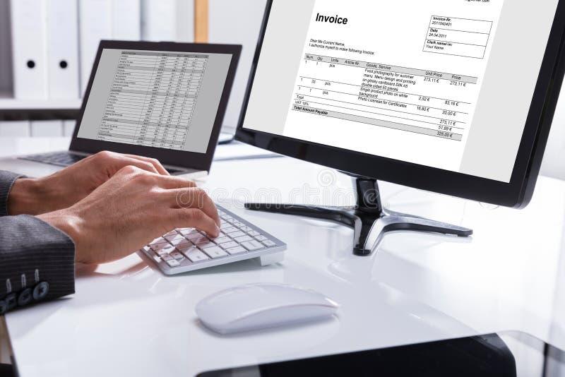De Computer van Businesspersonchecking invoice on stock foto
