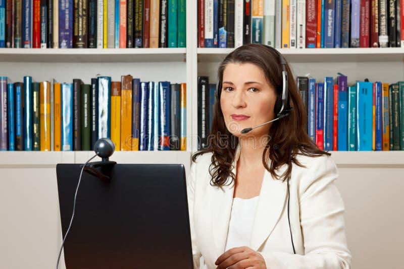 De computerhoofdtelefoon van de vrouwenbibliotheek webcam royalty-vrije stock afbeelding