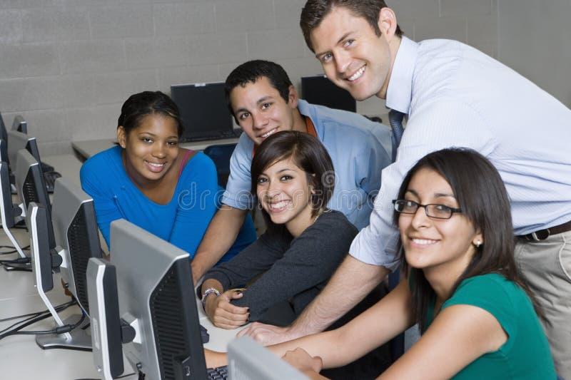 De Computerlaboratorium van leraarsand students in stock afbeeldingen