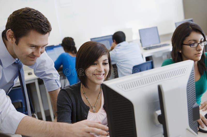 De Computerlaboratorium van leraarshelping student in stock afbeelding