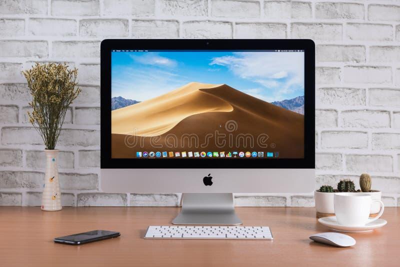 De computers van de IMacmonitor, toetsenbord, magische muis, iPhone, droge bloemen, koffiekop en cactusvaas op houten lijst royalty-vrije stock foto