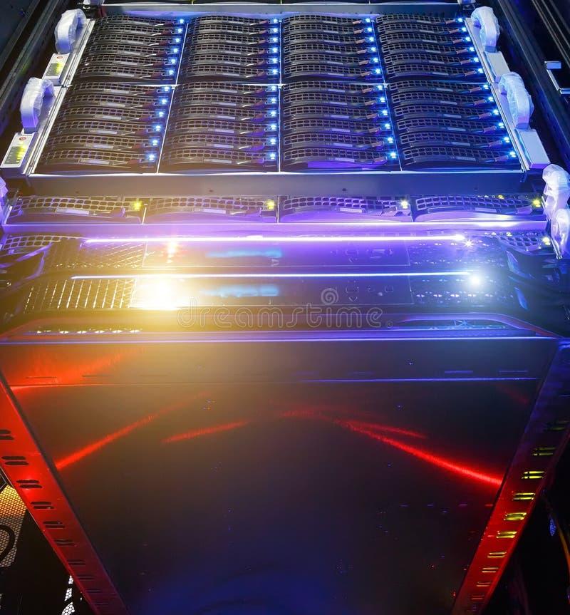 De computerserver zet op rek in de ruimte van het gegevenscentrum met rood verlichtingsalarm op bodemmening over de clusteropslag stock fotografie