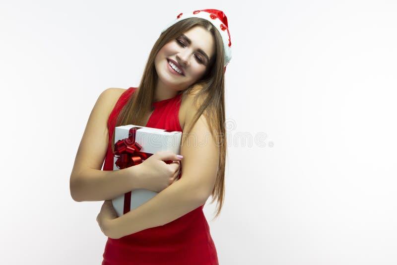 De Concepten van de Kerstmistijd Gelukkig Kalm Kaukasisch Wijfje in Rode Kleding en Santa Hat Het stellen met Witte omhoog Verpak royalty-vrije stock afbeeldingen