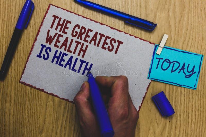 De conceptuele hand die tonend de Grootste Rijkdom is Gezondheid schrijven De bedrijfsfototekst die in goede gezondheid zijn is d royalty-vrije stock fotografie