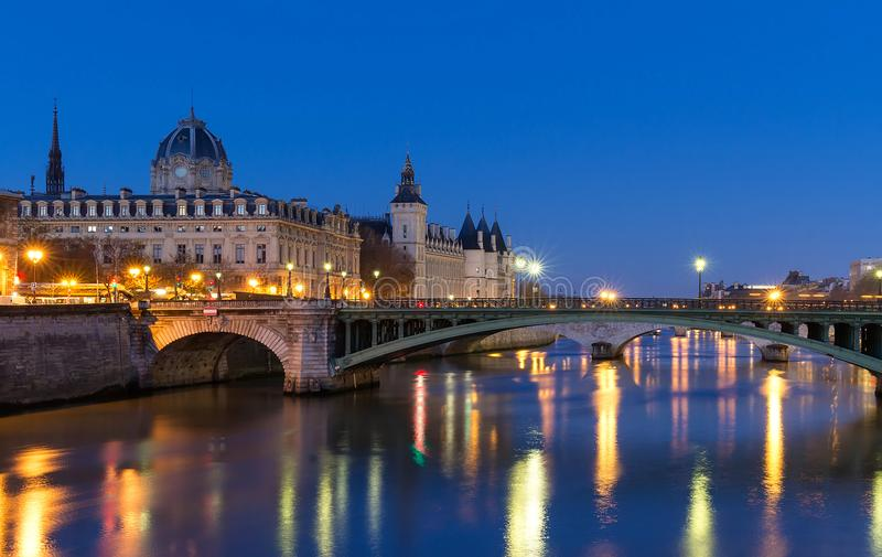 De Conciergeriebouw in Parijs, Frankrijk bij nacht met lichtenbezinning in het water van de Zegenrivier stock foto