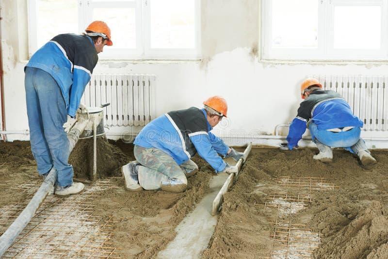 De concrete arbeider van de stukadoor aan het vloerwerk royalty-vrije stock afbeeldingen