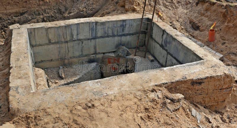 De concrete bunker voor rioleringskleppen bouwde een zandkuil in stock afbeelding