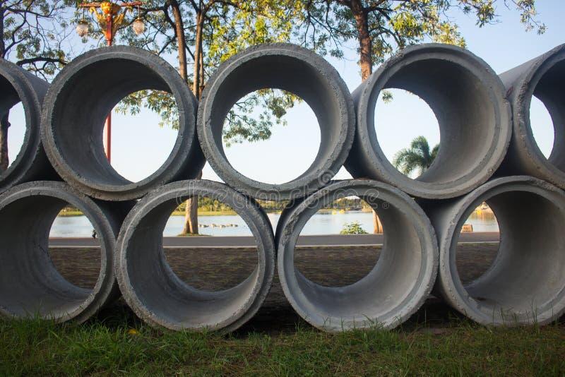 De concrete die drainagepijpen op bouwwerf worden gestapeld, kunnen bedelaars gebruiken stock afbeelding