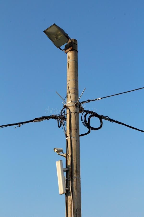 De concrete nutspool met veelvoudige elektrodraden en de camera met cel telefoneren torenzender en grote lichte reflector op bove stock afbeeldingen