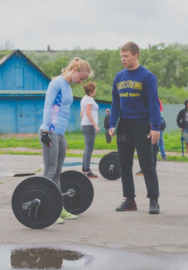 De concurrentie van Rusland Nikolskoe Juli 2016 voor crossfit sportief meisje in blauw bekijkt de staaf royalty-vrije stock afbeelding