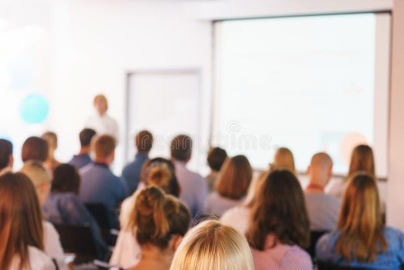 De conferentiedeelnemers luisteren aan de toespraak en de presentatie van de spreker in een speciaal publiek met een projector en stock fotografie