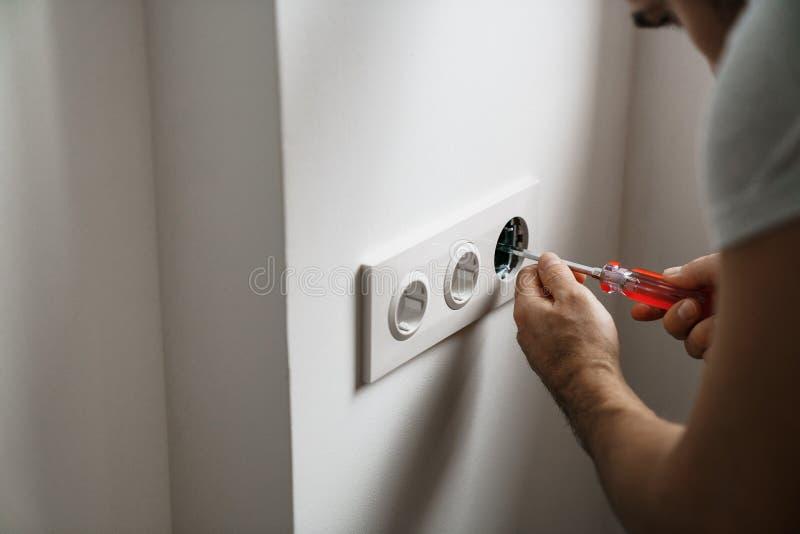De contactdoosmens van de reparatieelektriciteit met naakte handen Onjuiste veiligheid of reparatie van de elektroafzet royalty-vrije stock fotografie