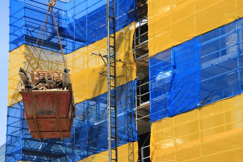 De container van het bouwafval hangt in de torenkraan boven het flatgebouw in aanbouw in het centrum van Th royalty-vrije stock fotografie