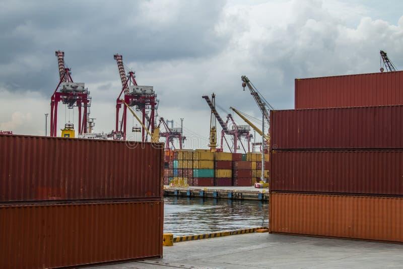 De container wordt verminderd van het schip dat de haven nadert stock foto's