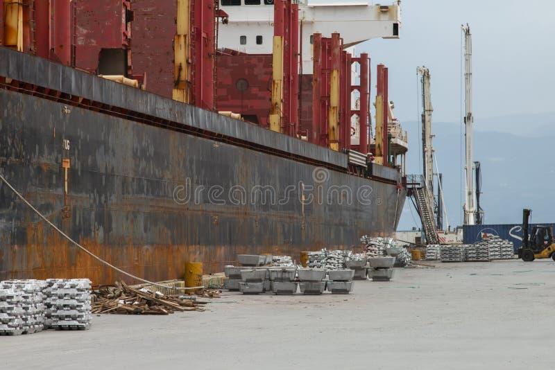 De container wordt verminderd van het schip dat de haven nadert stock fotografie