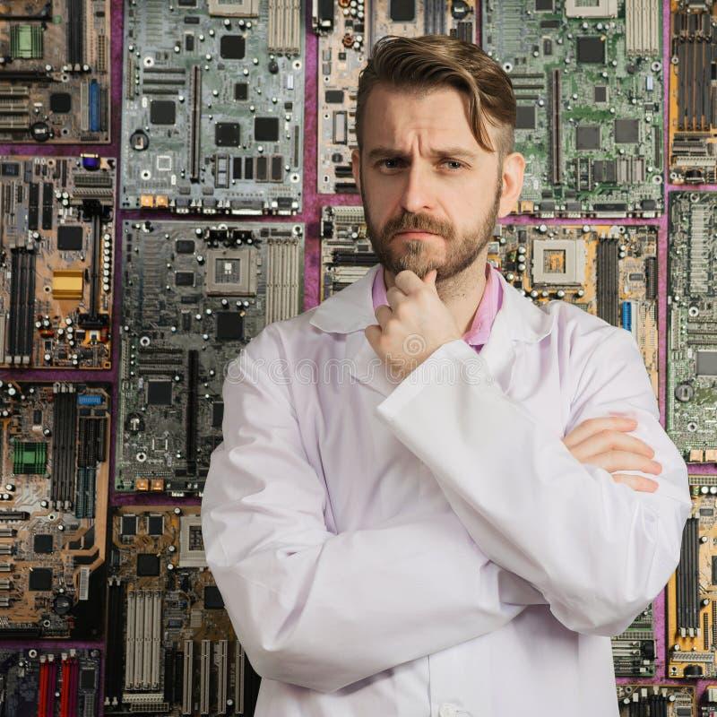 De contemplatieve elektronikaingenieur bevindt zich dichtbij de muur van motherboards stock afbeeldingen