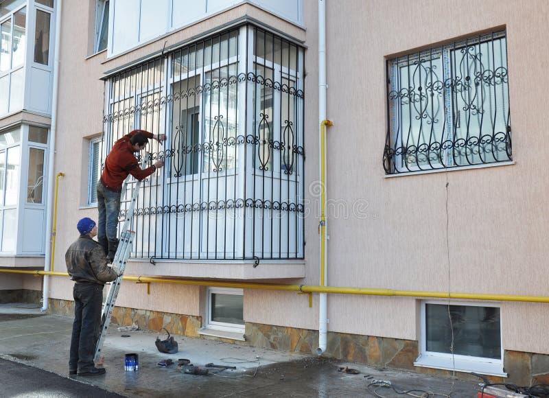 De contractanten installeren de veiligheidsbars van het vensterijzer stock fotografie