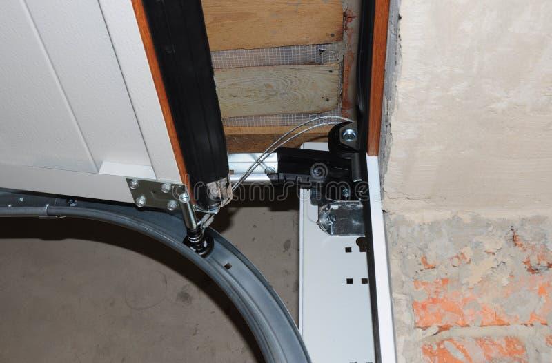 De contractantreparatie en installeert garagedeur Vervang de Gebroken Lente van de Garagedeur royalty-vrije stock foto's