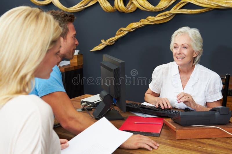 De Controle van Helping Couple To van de hotelreceptionnist binnen royalty-vrije stock foto's