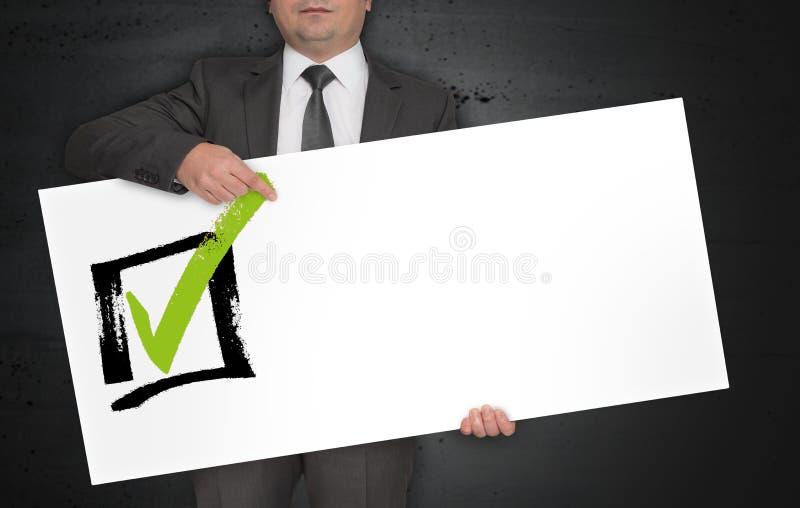 De controlelijstaffiche wordt gehouden door zakenman stock fotografie