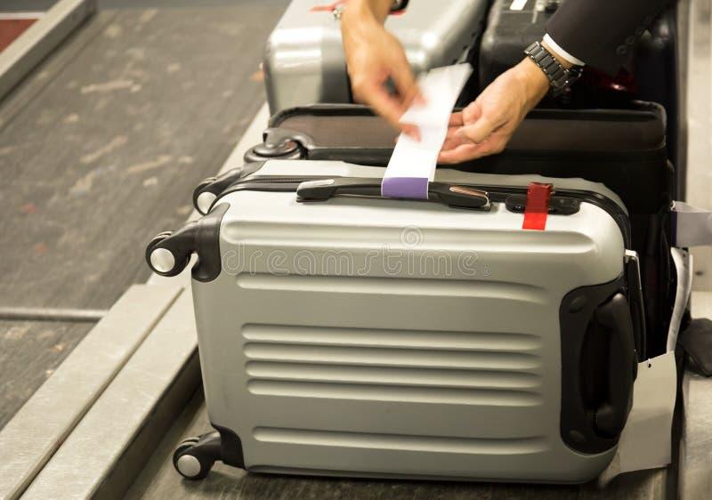 De controlewerknemer maakt een bagagemarkering aan koffer passenge vast royalty-vrije stock fotografie