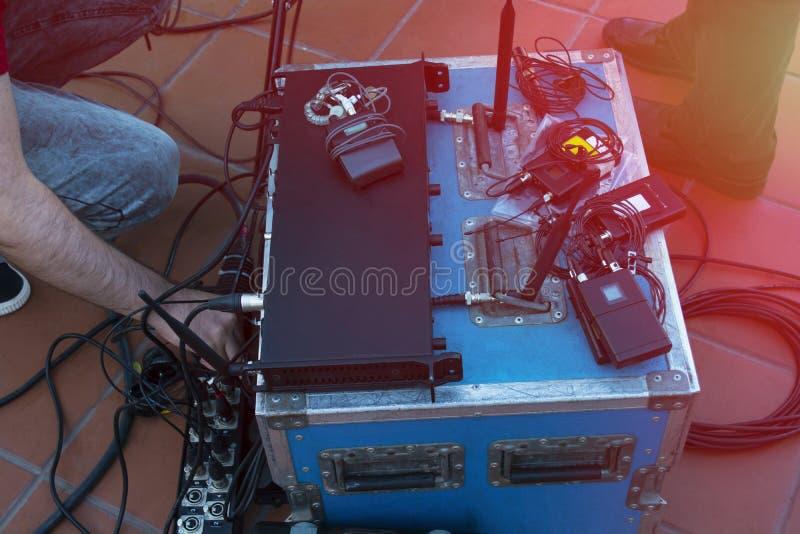 De correcte technicus en de lichtentechnici controleren de muziek tonen in overleg Het professionele audio, lichte paneel van het royalty-vrije stock foto