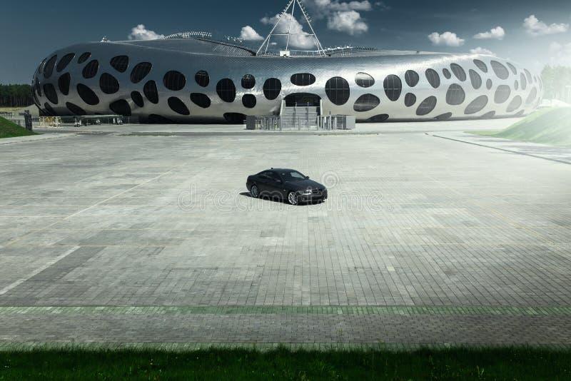 De Coupé van autobmw E92 die zich op kasseisteen leeg parkeerterrein dichtbij de moderne bouw bij dag bevinden royalty-vrije stock foto