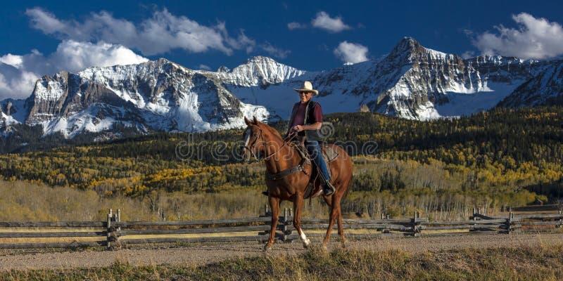 De cowboy berijdt paard over historische Laatste Dollarboerderij op Hastings royalty-vrije stock fotografie