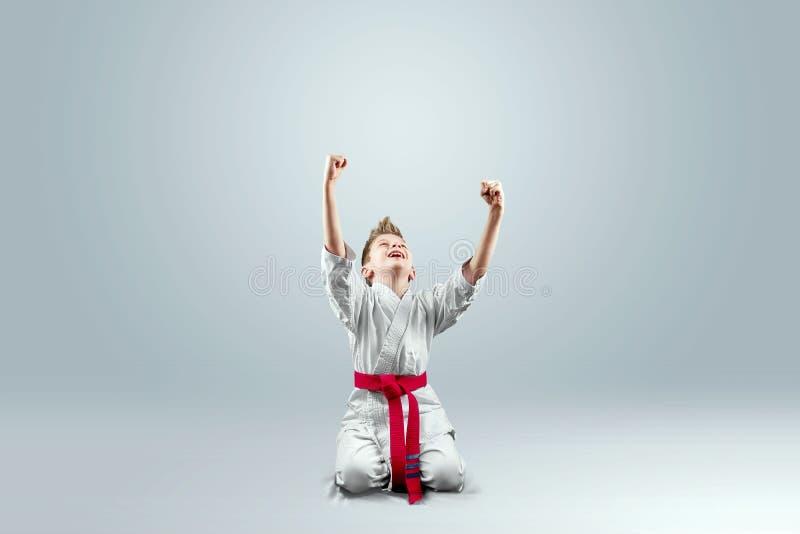 De creatieve achtergrond, een kind in een witte kimono verheugt zich overwinning, op een licht backgroundThe concept vechtsporten stock afbeelding