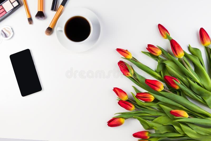 De creatieve achtergrond met maakt borstels, mobiele telefoon, omhoog kop van koffie en bloemen op witte achtergrond stock fotografie